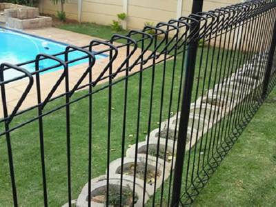 Black roll top fencing as swimming pool fence for a house.
