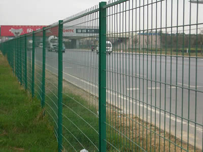 Many vehicles are driving on the highway with welded wire fence.