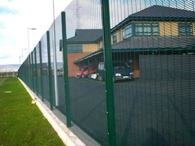Green vinyl-coated 338 security perimeter fencing keeps intruders out.
