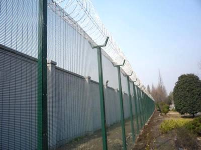 Green vinyl-coated prison fence with razor wire on top.