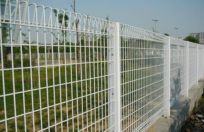 White vinyl-coated roll top fencing for a business area.