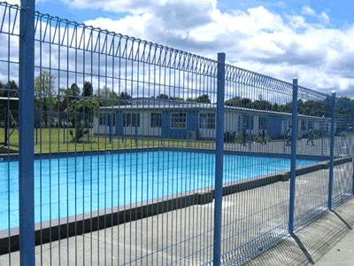 Blue pool fence manufactured according to law.